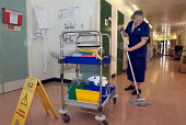 Domestic polishing the floor of a corridor, Homerton Hospital, Hackney, East London, employed by multinational ISS Mediclean cleaning services - Philip Wolmuth - 29-02-2004