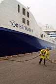 Dock workers haul the mooring ropes of a roll-on roll-off container ship arriving at Immingham Dock on Humberside - Philip Wolmuth - 02-04-2004