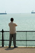 A refugee from Zimbabwe stares out to sea from the promenade near a Dover hotel used by Migrant Helpline to house asylum seekers awaiting decisions on their asylum applications. - Philip Wolmuth - 2000s,2004,african,africans,application,applications,Asylum Seeker,Asylum Seeker,BAME,BAMEs,black,BME,bmes,Diaspora,dispersal,dispersing,displaced,diversity,ethnic,ethnicity,foreign,foreigner,foreigne