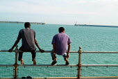Two refugees from Zaire look out to sea from the promenade near a Dover hotel used by Migrant Helpline to house asylum-seekers awaiting decisions on their asylum applications. - Philip Wolmuth - 21-07-2004