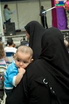 A Muslim woman in a hijab carries a small child at a community festival Paddington, London. - Philip Wolmuth - 2000s,2004,adult,adults,asian,BAME,BAMEs,black,BME,bmes,boy,boys,burka,burkas,burqa,burqas,child,CHILDHOOD,children,cities,city,communities,community,developer,developers,DEVELOPMENT,diversity,dress,e