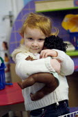 A white girl with a black doll at a pre-school nursery on Fisherton Estate, part of the Church Street Sure Start area, Paddington, London. - Philip Wolmuth - 14-01-2004