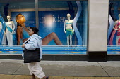 An overweight Afro-caribbean woman walks past a Marks & Spencer window display of swimwear in Oxford Street, London. - Philip Wolmuth - 19-05-2005