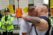Two men kiss in front of anti-gay Christians protesting on the route of the London Gay Pride march 2005. - Philip Wolmuth - 2000s,2005,activist,activists,adult,adults,against,anti gay,antigay,bible,biblical quote,biblical quotes,CAMPAIGN,campaigner,campaigners,CAMPAIGNING,CAMPAIGNS,carnival,Carnivals,CELEBRATE,CELEBRATING,