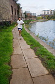 A jogger on the towpath by the Lea Navigation in the Lower Lea Valley, site of the 2012 Olympic Games. - Philip Wolmuth - 2000s,2005,Agency,Borough,brownfield,canal,cities,city,developer,developers,development,environment,exercise,exercises,exercising,Games,Gateway,jogger,joggers,jogging,LDA,Lea,leisure,lfL lifestyle & l