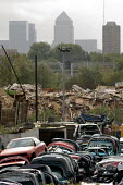 A vehicle scrapyard and builders' waste on derelict land in the Lower Lea Valley, site of the 2012 Olympic Games, close to Docklands and the Canary Wharf tower. - Philip Wolmuth - 26-10-2005