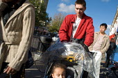 A father pushes his daughter in a buggy on Kilburn High Road, London. - Philip Wolmuth - 07-11-2005