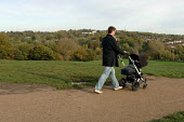 A father pushes a buggy over Parliament Hill, Hampstead Heath, London. - Philip Wolmuth - 2000s,2005,and,buggy,care,carer,carers,child,childcare,CHILDHOOD,CHILDMINDING,children,cities,city,council,DAD,DADDIES,DADDY,DADS,daughter,DAUGHTERS,early years,environment,families,FAMILY,father,FATH
