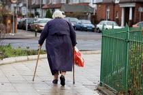 An elderly woman using walking sticks in south London. - Philip Wolmuth - 12-12-2005