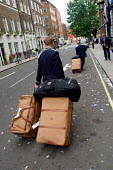 Porters carry luggage outside the Ritz Hotel, Piccadilly, London - Philip Wolmuth - ,2000s,2005,AFFLUENCE,AFFLUENT,bag,bags,Bourgeoisie,cities,city,EARNINGS,elite,elitism,employment,EQUALITY,high,high income,Hotel,HOTELS,Income,INCOMES,inequality,job,jobs,LAB LBR work,lfL lifestyle &