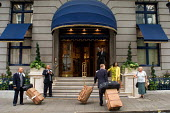 Porters carry luggage outside the Ritz Hotel, Piccadilly, London - Philip Wolmuth - ,2000s,2005,AFFLUENCE,AFFLUENT,bag,bags,Bourgeoisie,cities,city,EARNINGS,EBF,Economic,Economy,elite,elitism,employment,EQUALITY,high,high income,Hotel,HOTELS,Income,INCOMES,inequality,job,jobs,LAB LBR