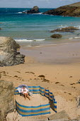 A woman reading a book as she relaxes on the beach at Trevone, in North Cornwall. - Philip Wolmuth - 13-08-2006