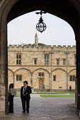 A college porter stands in the entrance to Chirst Church College, Oxford - Philip Wolmuth - 2000s,2006,Church,churches,college,COLLEGES,EDU Education,elite,elitism,entrance,EQUALITY,Higher Education,INEQUALITY,job,jobs,LAB LBR Work,Oxbridge,Oxford,people,privilege,privileged,university,worke