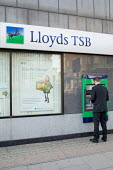 A man withdraws money from an ATM at a branch of Lloyds TSB bank in central London. - Philip Wolmuth - 06-02-2007