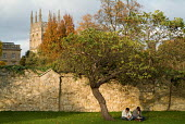 Two students read under a tree behind Christ Church College, Oxford - Philip Wolmuth - ,2000s,2007,AUTUMN,autumnal,book,books,church,churches,cities,city,cityscape,cityscapes,College,COLLEGES,communicating,communication,course,EDU education,FEMALE,garden,gardens,graduate,graduates,groun