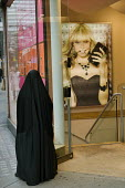 A Muslim woman wearing a niqab outside an Accessorize store Oxford Street London - Philip Wolmuth - &,2000s,2007,accessories,advert,ADVERTISED,advertisement,advertisements,advertising,ADVERTISMENT,adverts,apparel,asian,asians,BAME,BAMEs,belief,bigotry,Black,BME,bmes,bought,burka,burkas,burqa,burqas,