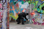 Young man paints graffiti on a wall at the South Bank, London. - Philip Wolmuth - 31-12-2007