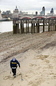 A man uses a metal detector at low tide on the south bank of the River Thames, London. - Philip Wolmuth - 31-12-2007