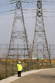 Security guard and electricity pylons at the Olympic Park site in Stratford. - Philip Wolmuth - 19-02-2008