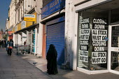 Closed and closing shops on the Harrow Road, London W9 - Philip Wolmuth - 2000s,2008,cities,city,closing,decline,down,DOWNTURN,EBF economy,economic,economy,FEMALE,High Street,highway,inner,ISLAM,ISLAMIC,London,monotheistic,MUSLEM,muslim,muslims,outlet,outlets,pavement,pedes