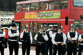 Police regulate traffic on Childrens Day at Notting Hill Carnival - Philip Wolmuth - 2000s,2008,ACE Arts Culture Entertainment,adult,adults,Afro-caribbean,and,BAME,BAMEs,black,BME,bmes,bus,bus service,BUSES,Caribbean,carnival,Carnivals,cities,city,CLJ,communities,community,community p