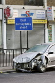 A wrecked car by a dual carriageway sign on the Harrow Road, West London. - Philip Wolmuth - 25-02-2008