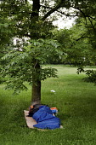 A man in a sleeping bag beneath a tree in Regents Park, London. - Philip Wolmuth - 01-06-2008