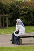 A Muslim woman wearing a headscarf sits on a park bench in London - Philip Wolmuth - 15-06-2008