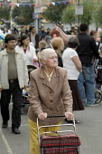 Elderly woman pushes a shopping trolly in Paddington, London. - Philip Wolmuth - 10-08-2008