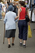 A young woman walks arm in arm with her grandmother in a small town in southern France on market day - Philip Wolmuth - 05-08-2008