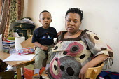 Fauzi Salifu and her son Sadiq in the one bedroom flat she shares with her husband and two children in Alexandra Court, a hostel used by Hackney Council as temporary accommodation for homeless familie... - Philip Wolmuth - 2000s,2009,accommodation,BAME,BAMEs,bedroom,BEDROOMS,Black,BME,bmes,boy,boys,child,CHILDHOOD,children,cities,city,council,Council Services,Council Services,Court,diversity,England,EQUALITY,ethnic,ethn