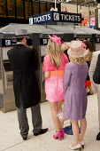 Passengers at Waterloo station buy train tickets to Ascot racecourse. - Philip Wolmuth - 18-06-2009