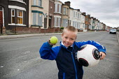 A boy plays outside his house in Anfield. Most of the other houses in the street are boarded up and scheduled for demolition by the Merseyside NewHeartlands partnership, financed by the Housing Market... - Philip Wolmuth - 19-06-2009
