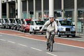 A man wearing a helmet and giving a hand signal to turn right cycles past a taxi rank outside St.Pancras International station, London. - Philip Wolmuth - 08-07-2009