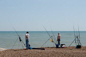 Two men with fishing rods on a shingle beach. - Philip Wolmuth - 2000s,2009,angler,anglers,angling,beach,beaches,coast,coastal,coastline,coastlines,coasts,enthusiast,enthusiasts,fisher,fisheries,fisherman,fishermen,fishers,fishery,fishing,Fishing Industry,hobbies,h