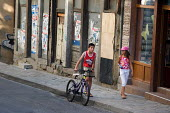 A girl and a boy walk past a closed shop in Veliko Tarnovo, the town has suffered as a result of the financial crisis. - Philip Wolmuth - 2000s,2009,bicycle,bicycles,BICYCLING,Bicyclist,Bicyclists,bike,bikes,boy,boys,Bulgaria,bulgarian,bulgarians,child,CHILDHOOD,children,closed,closing,closure,closures,communicating,communication,conver