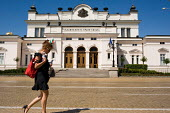 A young woman talking on a mobile phone passes the Bulgarian National Assembly, Sofia. - Philip Wolmuth - 2000s,2009,ACE,architecture,Assembly,building,buildings,Bulgaria,bulgarian,bulgarians,CELLULAR,cities,city,communicating,communication,conversation,culture,democracy,dialogue,Eastern Europe,eu,europea