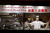A cook prepares food in the window of a Chinese takeaway noodle and dumpling restaurant in Oxford Street, London. - Philip Wolmuth - 2000s,2009,asian,asians,BAME,BAMEs,BME,bmes,casual,catering,chinese,diversity,EARNINGS,EBF Economy,employment,England,EQUALITY,ethnic,ethnicity,fast,fast food,fast food,fastfood,food,FOODS,Income,INCO