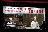 A cook prepares food in the window of a Chinese takeaway noodle and dumpling restaurant in Oxford Street, London. - Philip Wolmuth - 08-10-2009