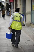 A cleaner with a mop and bucket walks down a street in central London. - Philip Wolmuth - 2000s,2009,BAME,BAMEs,black,BME,bmes,capitalism,capitalist,cities,city,cleaner,cleaners,CLEANING,cleansing,CONTRACTOR,contractors,diversity,EARNINGS,employment,EQUALITY,ethnic,ethnicity,Income,INCOMES