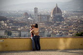 A young man and woman kiss on a terrace overlooking the Duomo, Florence, Italy. - Philip Wolmuth - 05-06-2010