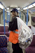A cleaner collects and bags discarded newspapers from a carriage at London Underground's Northumberland Park Depot, which services the 42 tube trains on the Victoria line. - Philip Wolmuth - 03-12-2009