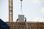 Construction workers on the roof of a new housing development in Maningtree, Essex - Philip Wolmuth - 15-07-2010