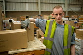 A Job Seekers Allowance claimant on a compulsory four week unpaid work placement in a warehouse on Stakehill Industrial Estate, Oldham, part of a Mandatory Work Related Activity welfare-to-work progra... - Philip Wolmuth - 07-10-2010