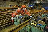 A worker in the Points and Crossings Shed of London Underground's Lillie Road Depot bends a replacement rail to match a curve in the track. The depot produces replacement track for the tube network an... - Philip Wolmuth - ,2010,2010s,administration,capitalism,capitalist,cities,city,contractor,contractors,cut,cutter,cutters,cutting,EBF,Economic,Economy,employee,employees,employment,engineer,engineering,Engineering Indus