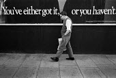 1983: You've either got it, or you haven't. A man walks past an advertising hoarding on the Harrow Road, West London. - Philip Wolmuth - 10-08-1983