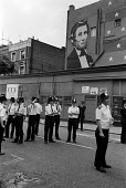 1981 police stand guard on the corner of Westbourne Park Road and Portobello Road beneath a mural of anti slavery American president Abraham Lincoln during the Notting Hill Carnival - Philip Wolmuth - 1980s,1981,ACE,adult,adults,American,americans,art,arts,cities,city,CLJ law justice,communities,community,culture,flag,flags,force,guard,highway,Lincoln,London,MATURE,metropolitan police service,mural