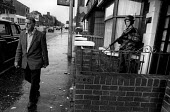 Man walks past a British soldier on patrol, Falls Road, Belfast, 1984 - Philip Wolmuth - (SLR), British Army,1980s,1984,armed,Armed Forces,arms,army,Catholic,Catholics,cities,city,conflict,conflicts,gun,guns,highway,Irish,L1A1,military,Northern Ireland,patrol,patrolling,pedestrian,pedestr