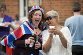 Royal Wedding street party in Kilravock Street, Queen's Park, West London. - Philip Wolmuth - 2010s,2011,alcohol,black,bottle,bottles,Champagne Bottle,cities,city,drink,drinker,drinkers,drinking,drinks,families,family,FEMALE,flag,flags,funny,hat,hats,Humor,HUMOROUS,HUMOUR,joking,laugh,laughing