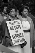 Workers at St.Mary's Hospital, Harrow Road, London, march in protest at the imposition of short-term contracts and the proposed closure of the hospital. - Philip Wolmuth - 1980s,1981,activist,activists,against,ancillary,BAME,BAMEs,Black,BME,bmes,CAMPAIGN,campaigner,campaigners,CAMPAIGNING,CAMPAIGNS,closed,closing,closure,closures,cuts,DEMONSTRATING,demonstration,DEMONST